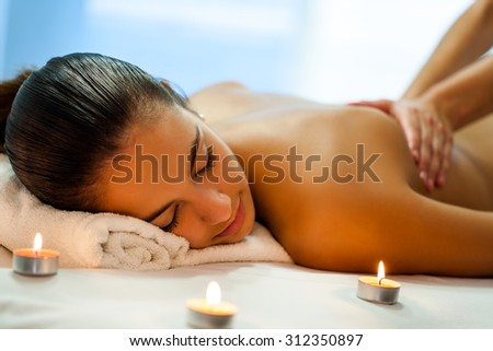 Close up portrait of attractive young woman having relaxing body spa treatment in dim candle light. Therapist in background massaging back. - stock photo