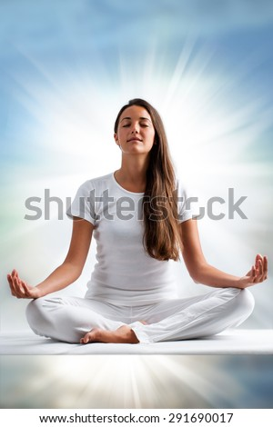 Close up portrait of attractive young woman meditating with eyes closed. Front view of woman dressed in white in yoga position with ray of light in background. - stock photo