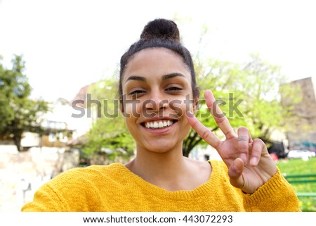 Close up portrait of attractive young woman taking selfie and gesturing peace sign   - stock photo