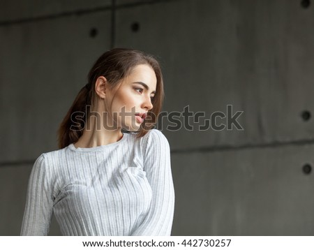 close up portrait of attractive young woman with long brunette red hair in front of the window near the wall - stock photo