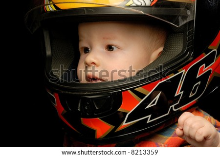 Close-up portrait of baby boy in motorcycle helmet holding left hand to his face - stock photo