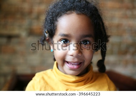 Close up portrait of beautiful African child looking at camera.  - stock photo