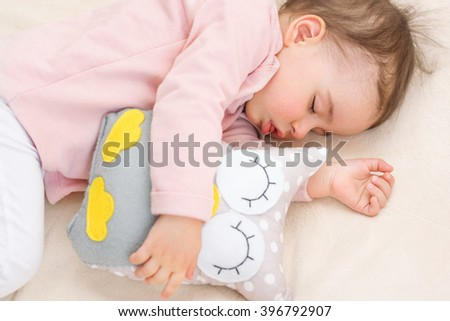Close-up portrait of beautiful asleep baby girl, toddler with an owl toy - stock photo