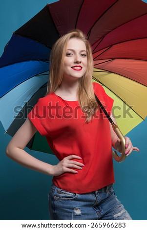 Close up portrait of beautiful blond female with rainbow umbrella background - stock photo