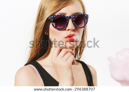 Close up portrait of beautiful blonde girl having fun and eating pink cotton candy. Wearing sunglasses with stars. Red lips. White background, not isolated. - stock photo