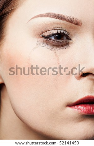 close-up portrait of beautiful crying girl with smeared mascara - stock photo