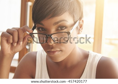 Close up portrait of beautiful dark-skinned female student with short haircut touching her spectacles, looking at the camera with serious expression sitting at the window preparing for exams indoors - stock photo