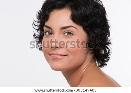 Close-up portrait of beautiful face of young adult woman with clean fresh skin. Middle-aged woman with black hair demonstrating face isolated on white. - stock photo