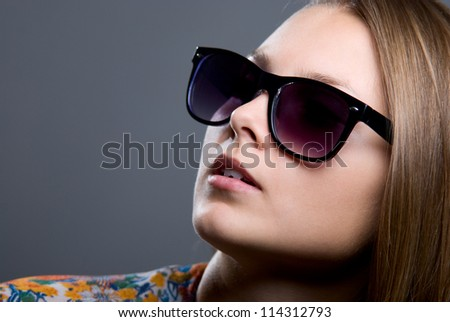 Close-up portrait of beautiful girl in sunglasses on a gray background - stock photo