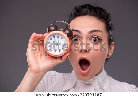 Close-up portrait of beautiful girl surprised looking at you and holding an alarm clock in her hand, with copy place isolated on grey background concept of time management - stock photo