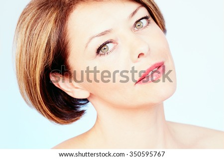 Close up portrait of beautiful middle aged woman with short brown hair, red lips and fresh makeup over blue background - beauty concept - stock photo