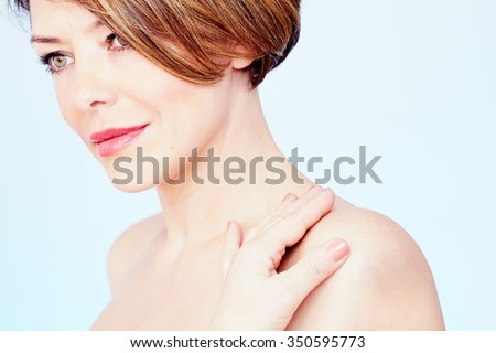 Close up portrait of beautiful middle aged woman with short brown hair, red lips and fresh makeup standing with hand on her shoulder and looking aside over blue background - beauty concept - stock photo