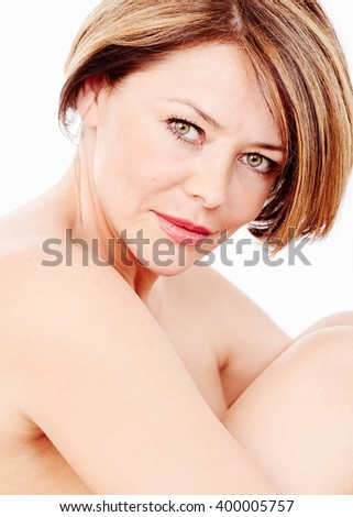Close up portrait of beautiful middle aged woman with short brown hair, red lips and fresh makeup hugging her knees over white background - beauty, skin care or anti aging concept - stock photo