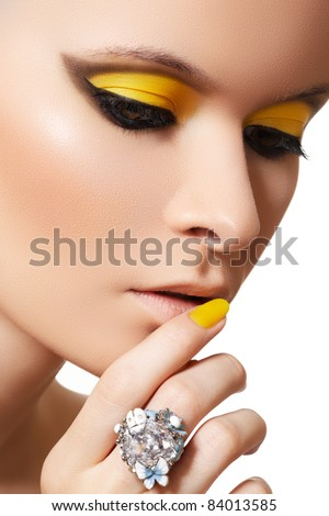 Close-up portrait of beautiful model face with neon bright yellow fashion make-up and with big crystal ring - stock photo
