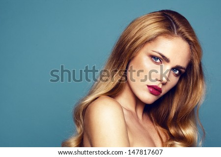 Close-up portrait of beautiful model with bright lips. Shooted on dark turquoise background  - stock photo