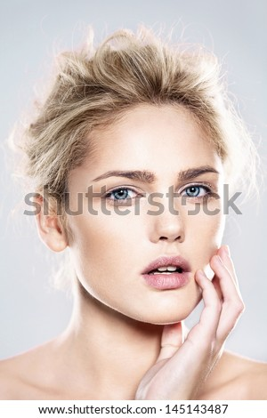 close-up portrait of beautiful model with natural make-up, shooted on blue background - stock photo
