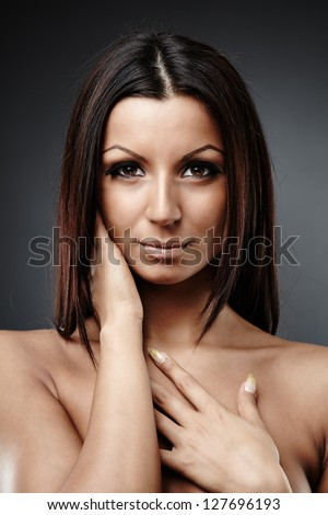 Close-up portrait of beautiful naked female model looking at camera, on gray background - stock photo