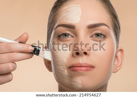 Close-up Portrait of beautiful smiling girl in spa applying facial cosmetic cream with brush on her face isolated on beige background looking at the camera - stock photo