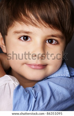Close-up portrait of beautiful smiling little boy, studio shot - stock photo