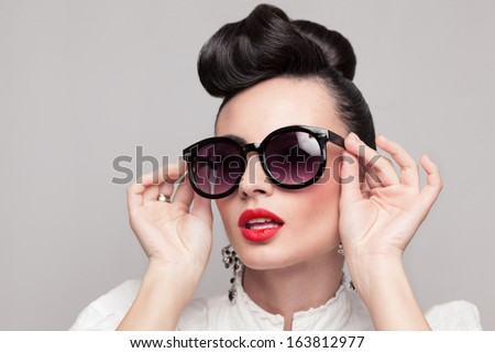 Close Up portrait of beautiful vintage styling model wearing round black sunglasses. Updo, large earrings - stock photo