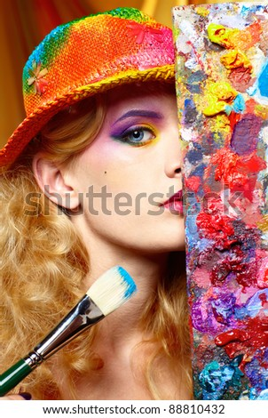 close-up portrait of beautiful woman artist looking from behind of palette - stock photo