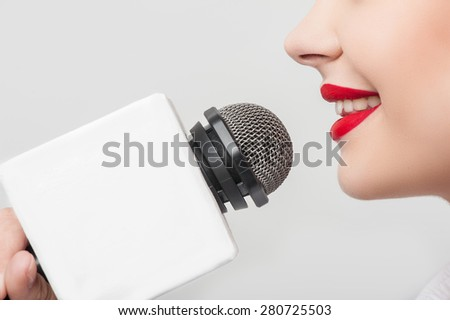 Close up portrait of beautiful woman reporter with Caucasian appearance, who is smiling and talking into the microphone while holding it with her right hand. She has bright red lips. - stock photo