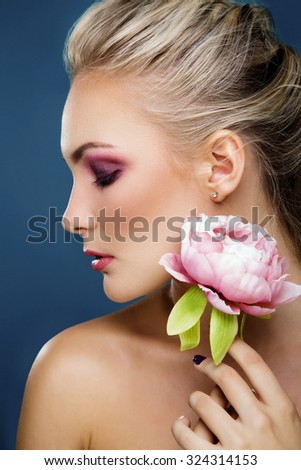 Close-up portrait of beautiful woman with fresh face holding peony flower in her hand, on blue background. Fashion photo.  - stock photo