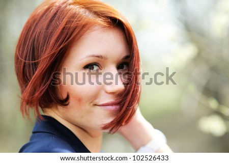 Close-up portrait of beautiful woman with red hair posing outdoors - stock photo