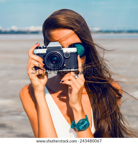 Close up Portrait of beautiful  woman with retro hipster camera having fun at the beach , wearing blue sunglasses and watch . - stock photo
