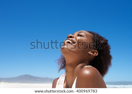 Close up portrait of beautiful young african woman laughing outdoors against sky - stock photo