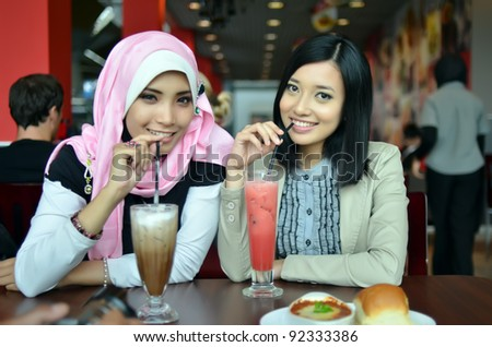 Close-up portrait of beautiful young Asian Muslim woman at cafe with lovely smiles - stock photo