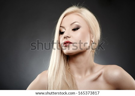 Close up portrait of beautiful young blonde over gray background - stock photo