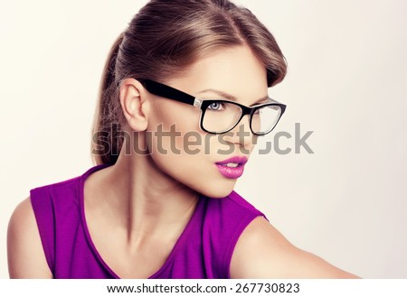 Close-up portrait of beautiful young blonde wearing stylish eyeglasses with purple lips. Attractive Caucasian businesswoman in spectacles.   - stock photo