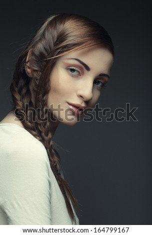 close up portrait of beautiful young blonde woman with creative braids hairdo  - stock photo