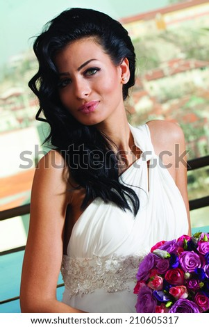 Close up portrait of beautiful young bride with long black hair. White dress, wedding bouquet of roses. - stock photo