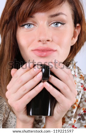Close-up portrait of beautiful young caucasian woman with black cup. - stock photo