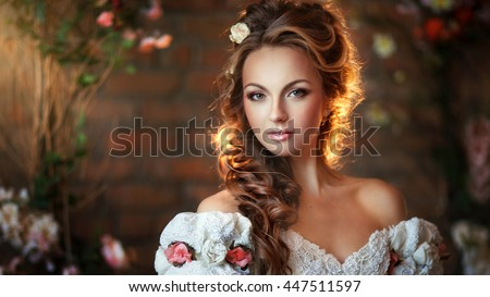 Close up portrait of beautiful young girl with curly hairstyle and flowers in her head.Magnificent princess in vintage dress and glowing hair. Amazing light.Art work. - stock photo