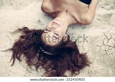 Close up portrait of beautiful young lady lying on dry cracked ground - stock photo