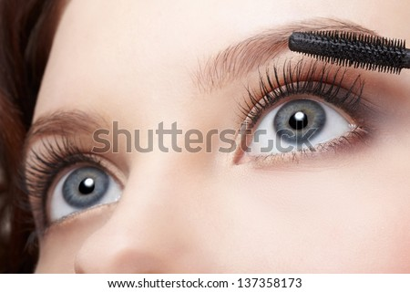 close-up portrait of beautiful young woman applying mascara - stock photo