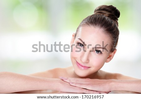 Close up portrait of beautiful young woman face while lying. Isolated on green background. Skin care or spa concept - stock photo