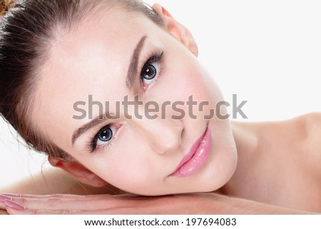 Close up portrait of beautiful young woman face while lying. Isolated on white background. Skin care or spa concept, caucasian - stock photo