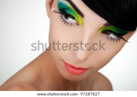 Close-up portrait of beautiful young woman's face with healthy clean skin and beautiful makeup looking to a side - stock photo