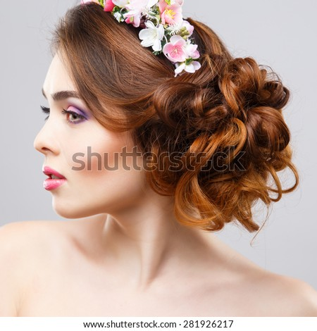 Close-up portrait of beautiful young woman with perfect make-up and hair-style with flowers in hair - stock photo