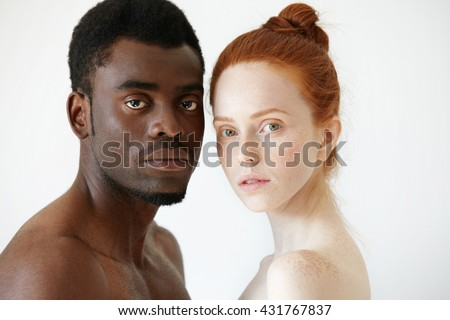 Close up portrait of black man and white woman standing isolated against white studio wall background, looking at the camera. Multi-ethnic love between young African male and redhead Caucasian female - stock photo