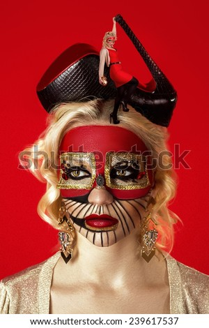 Close up portrait of blond curly woman with surrealistic make up face art - room, floor, lips like sofa, eyes two pictures, black high heels shoes hat, small woman figure, bright red background, crazy - stock photo