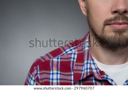 Close-up portrait of bottom-right corner of face. Bearded model in white T-shirt and maroon shirt posing seriously isolated on grey. - stock photo
