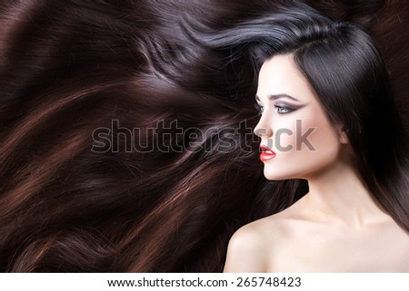 Close-up portrait of brunette girl in profile. She has long wavy hair. - stock photo
