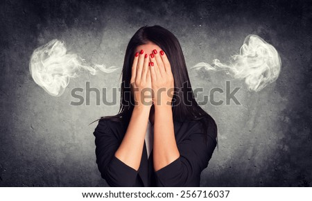 Close-up portrait of businesswoman hiding her face in her hands, with smoke from her ears. Raw concrete wall as backdrop - stock photo