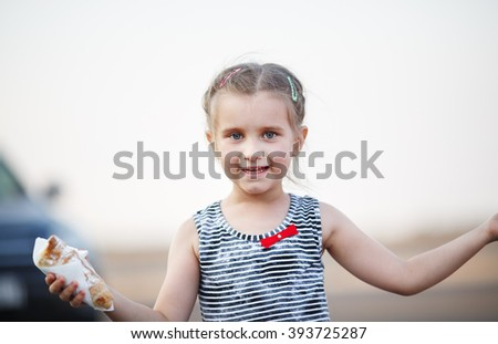 Close-up portrait of carefree happy smiling baby girl with a cake in hand.. Outdoors portrait of a child. Selective focus on model. - stock photo