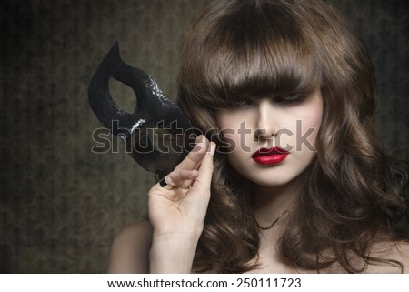 close-up portrait of charming brunette female with elegant hair-style and mysterious expression psing with black mask in the hand  - stock photo